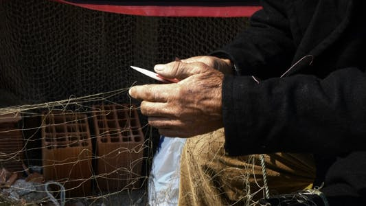 Thumbnail for Fisherman Repairs Fishnets Fishing Lines 1