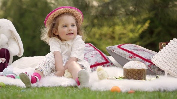 Thumbnail for Happy Child Sits On a Meadow Around Easter Decoration