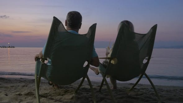 Cover Image for Mature Couple Relaxing On The Beach And Drinking Cocktails