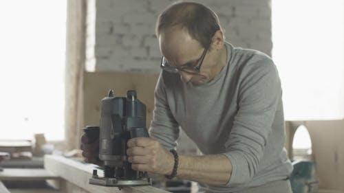 Aged Carpenter Attentively Treat Holzbrett von Plunge Router. Hersteller