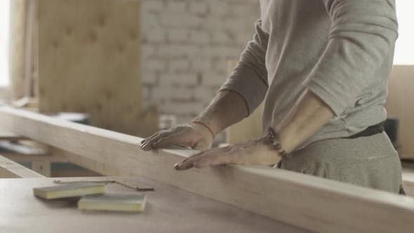 Professional Carpenter Checking Surface Of Wooden Board After Treatment.