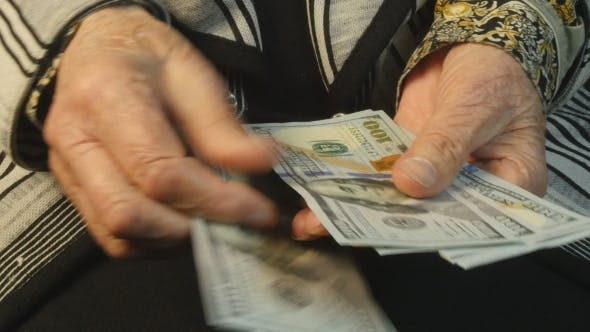 Cover Image for Old Woman Hands Counting Hundred Dollar Bills