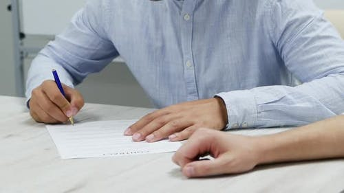 Close-up Businessman Hand Putting Signature on Paper. Signs a Contract in Slow Motion.
