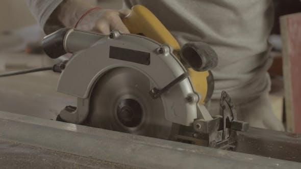 Carpenter Careful Cut Wooden Board On Straight Line Of Metal Balk