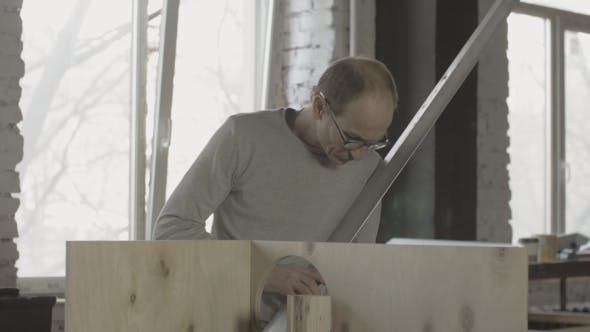 Thumbnail for Carpenter Search Something Among Woodworking Materials. Hold Metal Balk In Hands