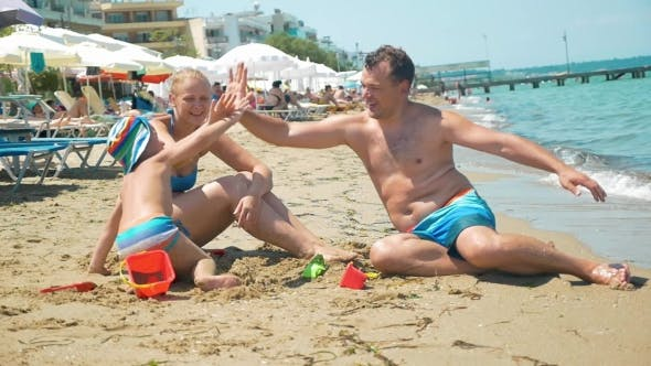 Family Of Three Giving Hi-fives On The Beach