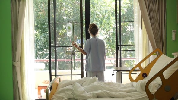 Young Sick Woman In Hospital At Window. Stressful and Upset