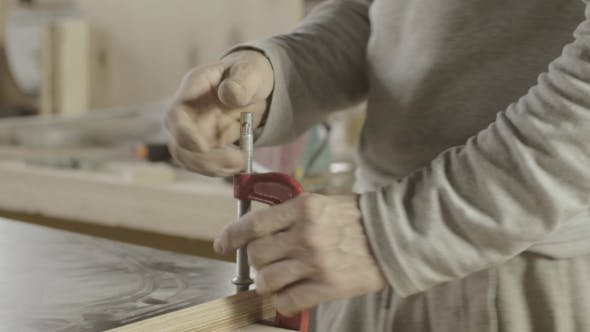 Professional Carpenter Fixing Wooden Board By Metal Clamps