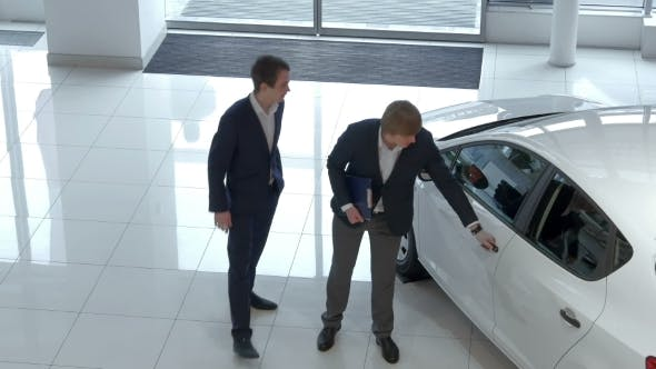 Salesman Demonstrating The Car To Buyer