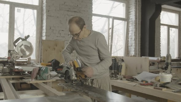 Woodworker Fixing Circular Saw On Edge Of Wooden Board On Work Table