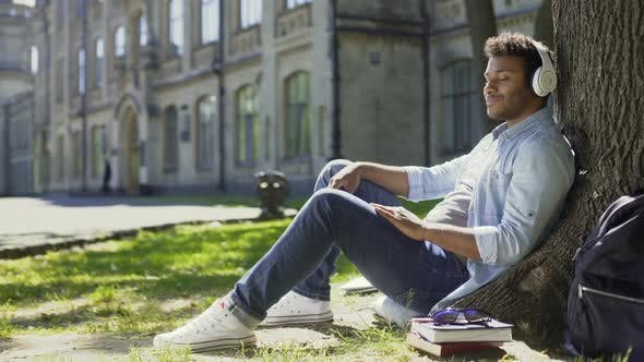 Thumbnail for Mixed Young Male Sitting Under Tree in Headphones, Eyes Closed, Enjoying Music