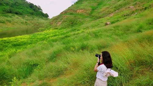 Young Asian female traveler is enjoying the beautiful scenery of the mountains and the green fields.