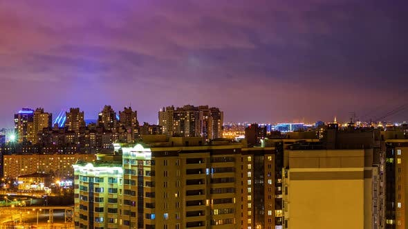 Night cityscape, Timelapse. Lights of buildings on the skyline. Cars lights on the streets