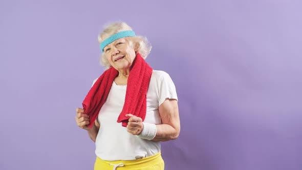 Ältere Sportlerin mit Stirnband und rotem Handtuch am Hals, Blick in die Kamera