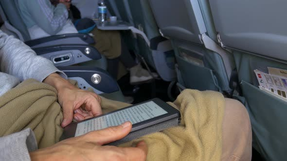 Woman reading ebook sitting inside airplane, travel vacation technology concept