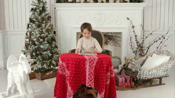 Thumbnail for Smiling Kid Boy Sitting at Table and Playing with Tablet During Christmas Time