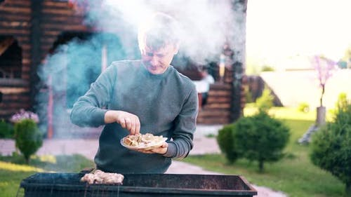 Young Man Stands on the Background of a Summer House Lays Meat on Barbecue Grill