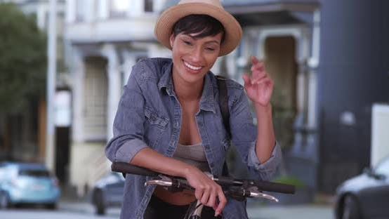 Pretty African American woman on bicycle smiling and happy in San Francisco