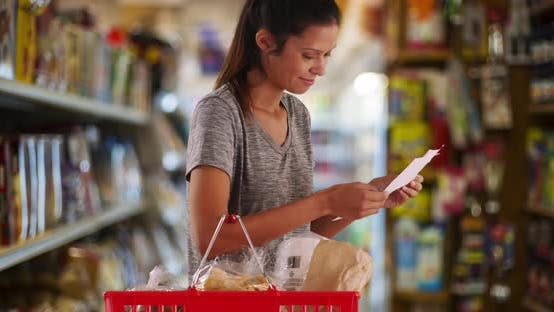 Thumbnail for Young wife or mother with shopping list looking for item in grocery store