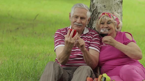 Thumbnail for Family Picnic. Senior Old Grandparents Couple in Park Using Smartphone Online Browsing, Shopping