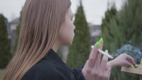 Thumbnail for Close Up Pretty Young Smoking Girl Painting on Canvas While Sitting in the Backyard Outdoors
