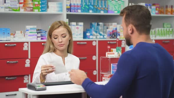 Young Female Druggist Dealing with a Male Customer