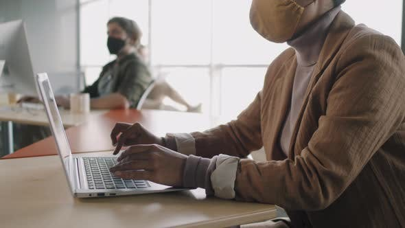 Businesswoman in Face Mask Working on Laptop