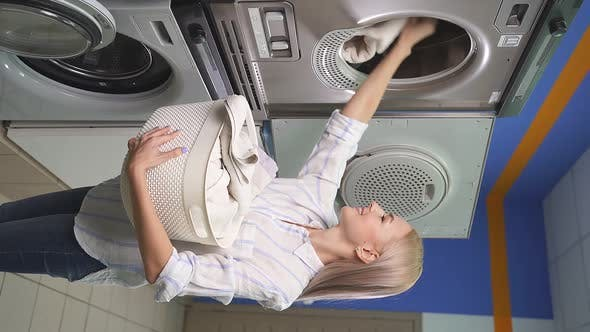 Smiling Attractive Woman in a Public Laundry Room