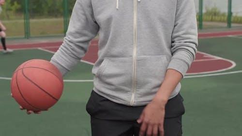 Mann mit Dreadlocks posiert auf Basketballplatz