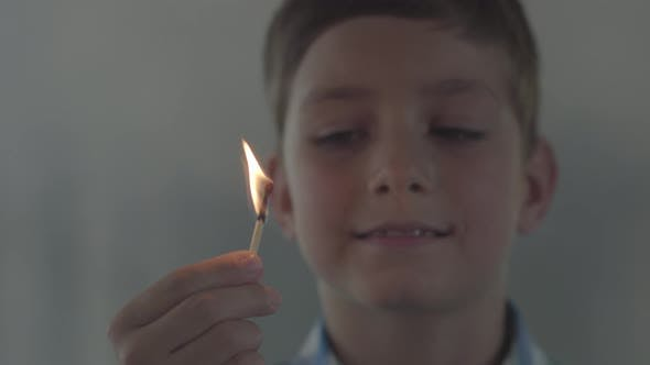 Thumbnail for Close-up Portrait of Little Boy Playing with the Matches in the Dark Smoky Room. The Child Lit
