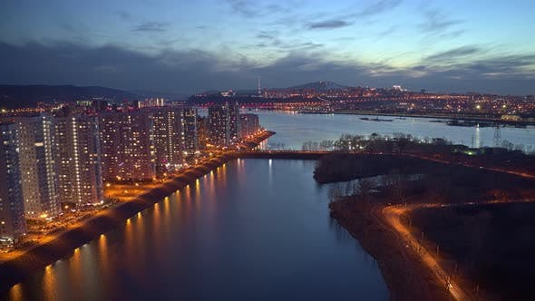Aerial Hyperlapse of a Residential Area on the Riverbank at Sunset