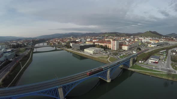 Thumbnail for Aerial view of a train passing on a Blue Bridge, Maribor