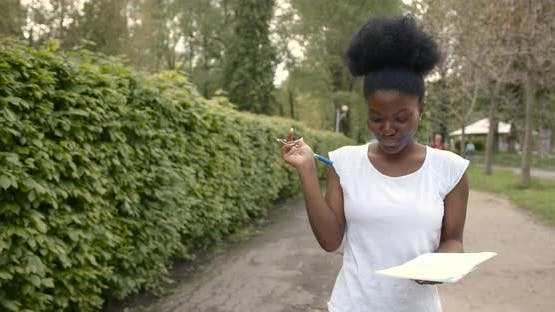 Black Woman Walk with Notebook in the Park