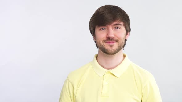 Thumbnail for Healthy Handsome Bearded Man Looking To Camera with Smile Wearing Yellow Shirt and Isolated on Grey