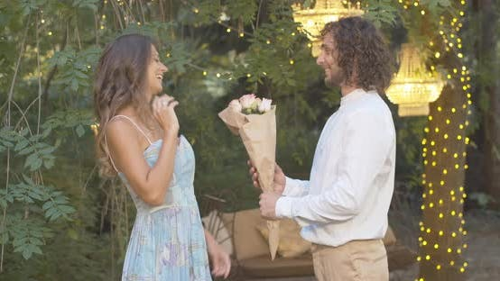 Thumbnail for Happy Young Man Giving Bouquet of Roses To Beautiful Caucasian Woman. Cheerful Beautiful Girlfriend