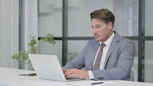 Middle Aged Man Working on Laptop in Office