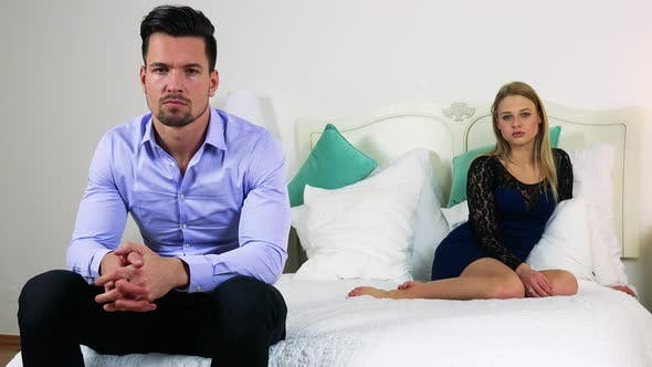 Thumbnail for A Young Couple on the Bed, Man Is in the Foreground, They Look at the Camera with Serious Faces