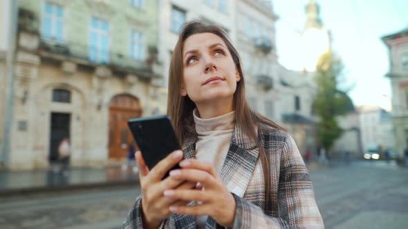 Woman Walking Down an Old Street and Using Smartphone, Taking Photos of Buildings Around