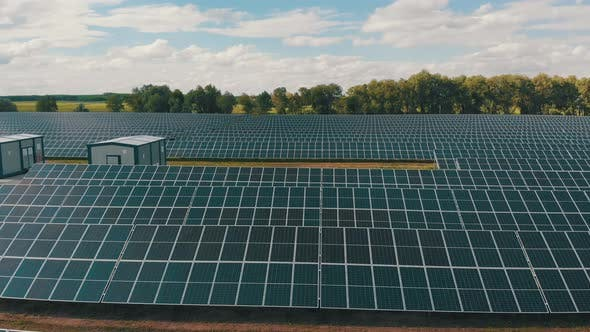 Thumbnail for Aerial View of Solar Power Station. Panels Stand in a Row on Green Field. Summer