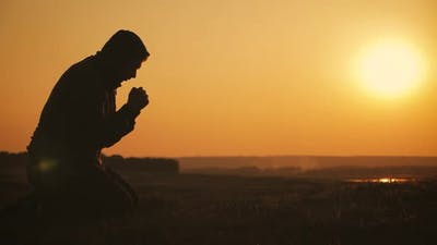 Silhouette Young Man Praying Outside at Beautiful Sunset. Male Asks for Help Finding Solace in Faith