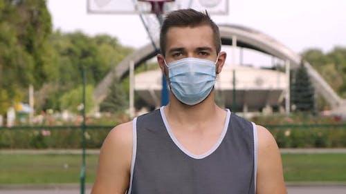 Porträt des Basketballspielers in einer medizinischen Maske stehend auf dem Spielplatz und Blick auf die Kamera
