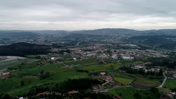 Thumbnail for Aerial view of green hillside and rural area with old houses, environment