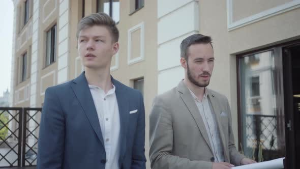 Thumbnail for Portrait of Two Cute Confident Men in Formal Wear Walking on Terrace Discussing New Project