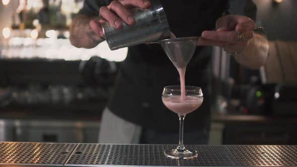 Thumbnail for Barman Pouring Pink Milk Cocktail Through a Sieve in High Glass on Bar Counter