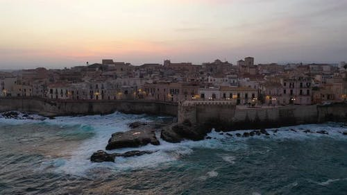 A Bird's Eye View of Ortigia Island at Sunset. Sailing Ship Out of the Bay