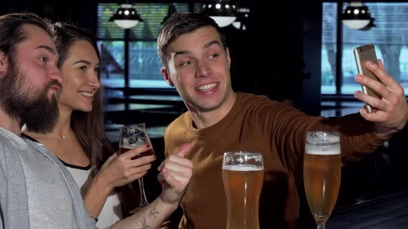 Thumbnail for Group of Friends Taking Selfies with Smart Phone, While Drinking Beer Together
