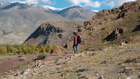 Woman Backpacker Hiking on Hills in Steppe