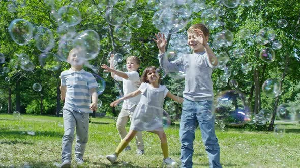 Cover Image for Funny Little Kids Chasing Soap Bubbles in Park