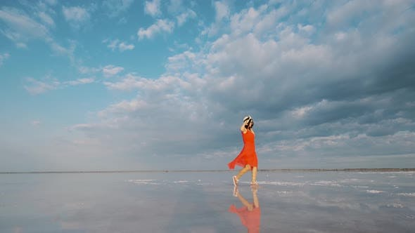 Thumbnail for Portrait of a Young Woman in a Fluttering Dress. Girl Traveler Walks on a Pink Salt Lake