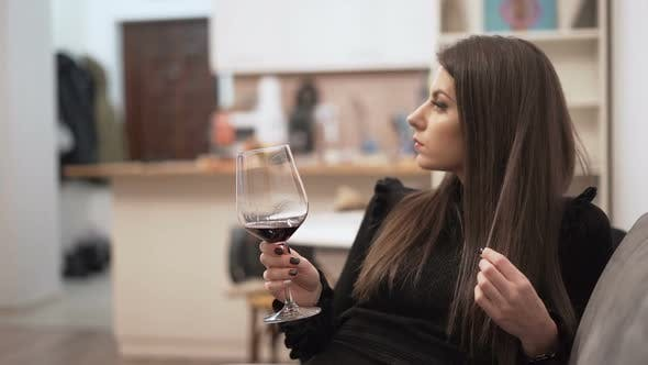 Thumbnail for Beautiful Woman in Black Dress Holding Glass of Wine and Playing with Her Long Hair